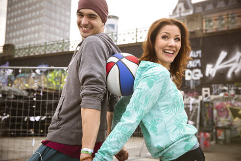 Happy young couple with basketball outdoors - SUF000078