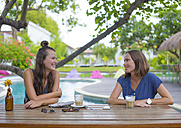 Two happy woman sitting at table at the poolside talking - KNTF000238