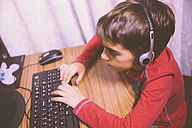 Boy sitting at desk using computer - ERLF000147