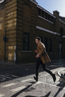 Young man in a hurry crossing urban street - BOYF000109