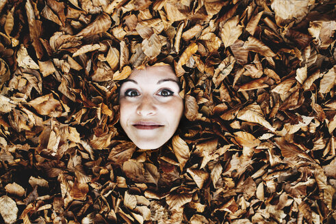 Woman's face in between autumn leaves - GEMF000766