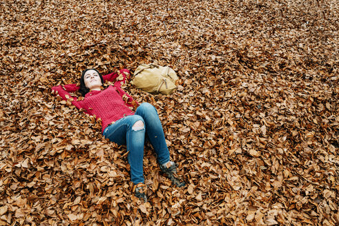 Woman relaxing on forest soil covered with autumn leaves - GEMF000769