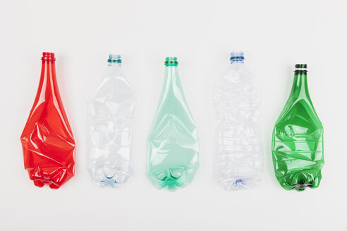Row of five different empty flexed plastic bottles on white ground - GWF004641