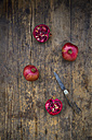Two whole and two halves of organic pomegranate and a pocket knife on wood - LVF004583