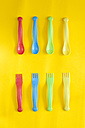 Rows of colourful plastic spoons and plastic forks on yellow background - VABF000261
