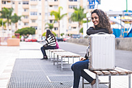 Spain, Tenerife, portrait of smiling teenage girl sitting on a bench with her case - SIPF000216