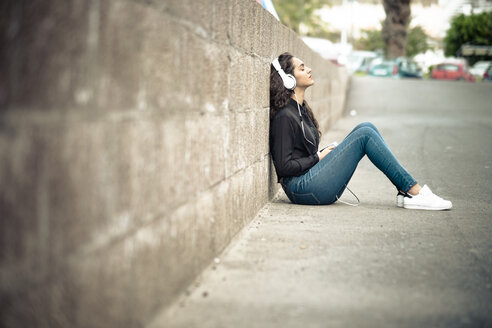 Teenage girl leaning against wall listening music with headphones - SIPF000219
