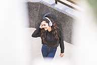 Smiling teenage girl listening music with headphones - SIPF000222