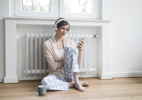 Woman at home sitting on floor with cell phone and headphones - FMKF002425