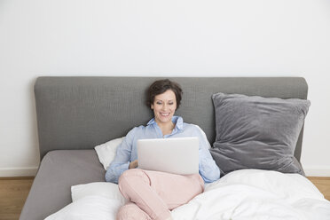 Happy woman lying on bed using laptop - FMKF002431