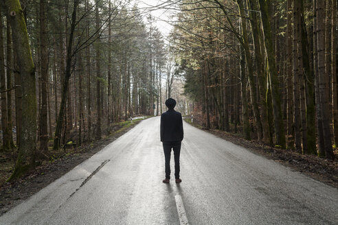 Germany, back view of young man dressed in black standing on empty country road - TCF004934
