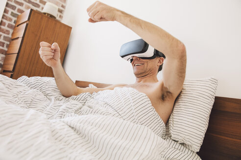 Man in bed wearing virtual reality glasses steering - MFF002734