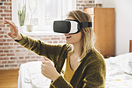 Woman wearing virtual reality glasses using her hands - MFF002743