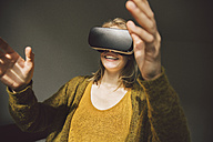 Woman wearing virtual reality glasses using her hands - MFF002746