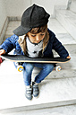 Boy sitting on stairs holding skateboard - VABF000271