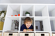 Portrait of playful boy in shelf - VABF000274