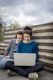 Happy teenage couple sitting outdoors with laptop and headphones - EGBF000136