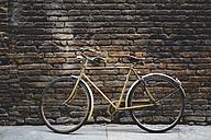 Vintage bicycle leaning against a brick wall - GIOF000788