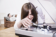 Young woman operating record player - FMKF002435
