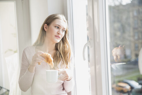 Portrait of young woman with croissant and cup of coffee looking through window - FMKF002447