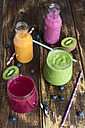 Glasses of four different smoothies and fruits on wood - SARF002610
