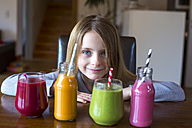 Portrait of smiling girl sitting at table with four different smoothies at choice - SARF002613