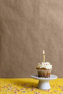 Cup cake with lighted candle sprinkled with sugar granules on a cake stand - VABF000286