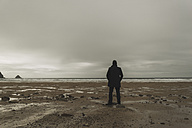 France, Bretagne, Finistere, Crozon peninsula, man standing on the beach - UUF006644