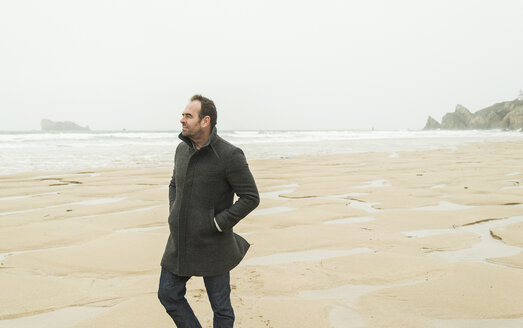 France, Bretagne, Finistere, Crozon peninsula, man walking on the beach - UUF006647