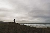 France, Bretagne, Finistere, Crozon peninsula, man standing at the coast under cloudy sky - UUF006650
