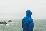 France, Bretagne, Finistere, Crozon peninsula, man standing at the coast with hooded jacket - UUF006653