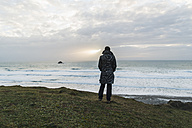 France, Bretagne, Finistere, Crozon peninsula, woman standing at the coast - UUF006656
