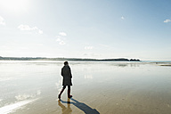 France, Bretagne, Finistere, Crozon peninsula, woman walking on the beach - UUF006659