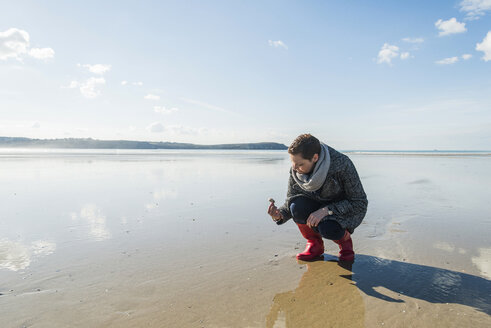 France, Bretagne, Finistere, Crozon peninsula, woman finding a seashell on the beach - UUF006662