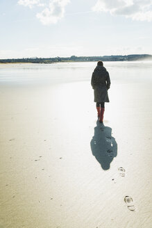France, Bretagne, Finistere, Crozon peninsula, woman walking on the beach - UUF006668