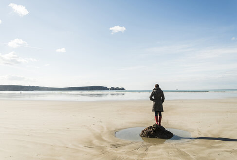 France, Bretagne, Finistere, Crozon peninsula, woman standing on the beach - UUF006671