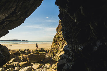 France, Bretagne, Finistere, Crozon peninsula, woman walking on the beach as seen from rock cave - UUF006674