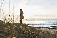 France, Bretagne, Finistere, Crozon peninsula, woman standing at the coast - UUF006683