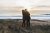 France, Bretagne, Finistere, Crozon peninsula, couple kissing at the coast at sunset - UUF006689