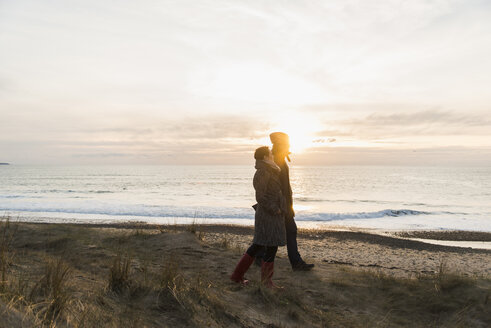 France, Bretagne, Finistere, Crozon peninsula, couple walking at the coast at sunset - UUF006692