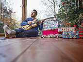 Man sitting on floor and playing electric guitar by Christmas tree - RHF001296