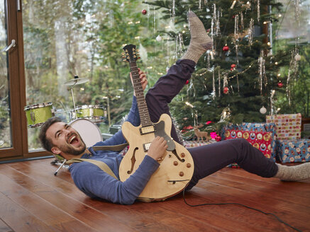Man playing electric guitar in front of Christmas tree - RHF001299