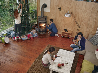 Friends preparing for Christmas Eve in cozy living room - RHF001302