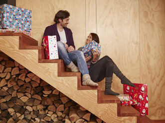 Happy couple sitting on wooden stairs holding Christmas presents - RHF001308