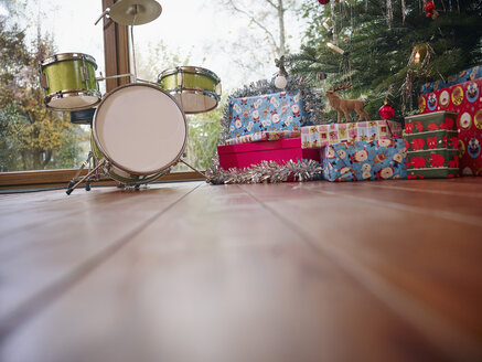 Christmas presents wrapped in colorful wrapping paper under Christmas tree - RHF001311
