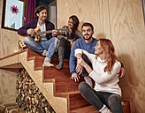 Friends sitting on wooden stairs playing guitar - RHF001314