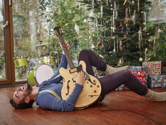 Man playing electric guitar in front of Christmas tree - RHF001317