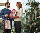 Couple standing in front of Christmas tree - RHF001320