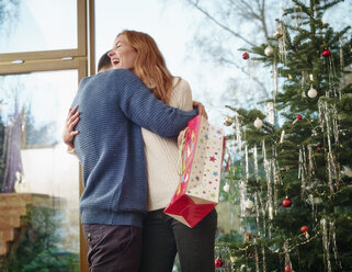 Couple standing in front of Christmas tree - RHF001323