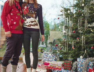 Couple standing in front of Christmas tree wearing Christmas jumpers - RHF001326